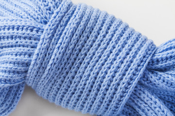 Light blue knitted scarf on a light background. Knot of a scarf in the form of a butterfly. Closeup