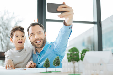 Precious moment. Joyful young man sitting at the table next to his little son and taking a selfie with him in the office while the boy putting bunny ears on him