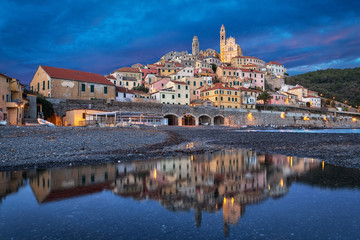Fototapete - Old ligurian town Cervo reflecting in water at dusk, Province of Imperia, Liguria, Italy