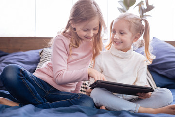 Family. Lovely delighted fair-haired girls smiling and using their tablet while sitting on the bed