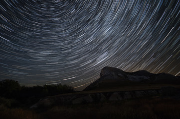 Beautiful star trails time-lapse over the hills. Polar Star at the center of rotation.Lateral light from the full moon on the chalk hills.