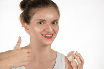 Young brunette woman applying makeup on skin foundation and smiling on white background