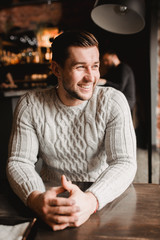 Man in cafe. lifestyle portrait of cute boy in sweater. Rustic styling.