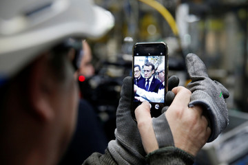An employee uses a mobile phone to make of picture of French President Emmanuel Macron as he visits Toyota's automobile manufacturing plant in Onnaing