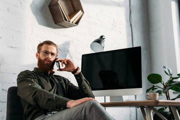 handsome businessman talking by smartphone and looking away