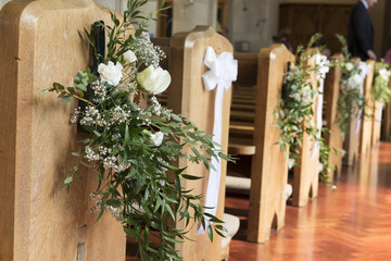Church benches decorated with flowers at a wedding ceremony