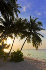Sonnenuntergang am Maledivenstrand mit Hängeschaukel
