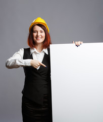 Photo of brunette builder in yellow helmet pointing finger clean sheet of paper