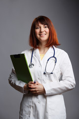 Photo of young female doctor with phonendoscope and folder in hand