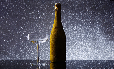 Image of bottle of champagne in gold wrapper with empty wine glass