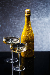 Festive image of bottle of champagne in gold wrapper with two wine glasses