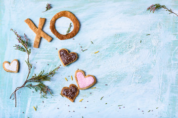 top view of heart shaped cookies, XO biscuits and green branches with flowers on turquoise surface