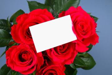 Blank white gift card on a bed of red rose petals, ready for your message.