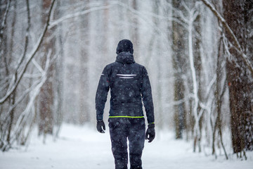 Photo from back of man in sports clothes on run in winter