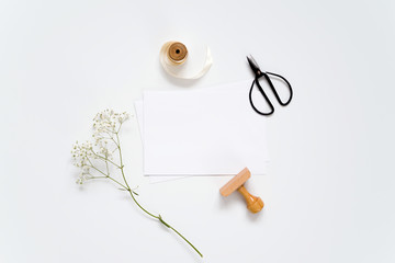 Cards and flowers on a white table. Mockup.