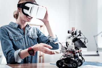 Under reality. Young woman touching virtual mask and expressing positivity while looking at robot