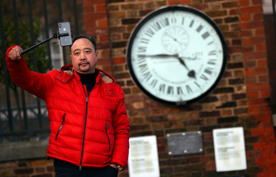 A man takes a selfie in front of the Shepherd 24-hour Gate Clock, which was installed in 1852 and shows Greenwich Mean Time (GMT) in Greenwich Park in London