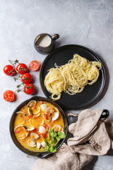Vongole in tomato cream sauce for pasta in cast-iron pan with textile and black plate with cooked spaghetti over gray texture background. Top view, space