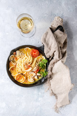 Pasta spaghetti Vongole in tomato cream sauce in cast-iron pan with textile and glass of white wine over gray texture background. Top view, space