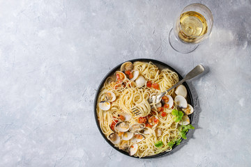 Pasta spaghetti Vongole in tomato cream sauce in black plate with fork and glass of white wine over gray texture background. Top view, copy space