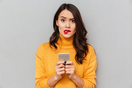 Worried brunette woman in sweater with smartphone bites her lip