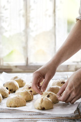 Raw unbaked buns. Ready to bake homemade Easter traditional hot cross buns on baking paper over white wooden table. Window at background. Female hands make a cross. Natural day light. Rustic style.