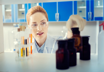 Let me see. Selective focus on a mature lady wearing safety glasses standing in a lab and taking a dark brown bottle with a chemical substance.