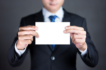 Businessman holding blank advertisement card with copy space