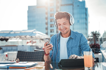No time for worries. Waist up shot of guy wearing headphones working on his touchpad and smiling while listening to his favorite music outdoors.
