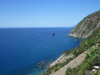 Costa selvaggia con mare imbarcazioni e borgo marino