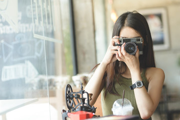 Happy Asian woman holding vintage camera in cafe.