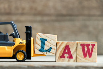 Toy yellow forklift hold letter block L to complete word law on wood background