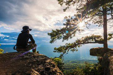 man watching the sunset from top of mountain