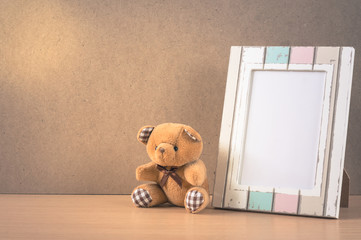 Bear doll with picture frame,vintage color filtered.