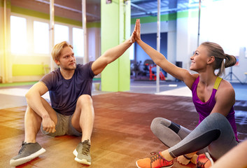 happy couple making high five in gym