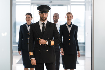 handsome pilot at airport with his team looking at camera Wall mural