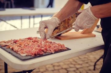 Closeup on chef hands slices prosciutto Italian delicatessen, restaurant party background. Festive time