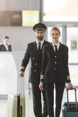 happy male and female pilots walking by airport lobby with suitcases