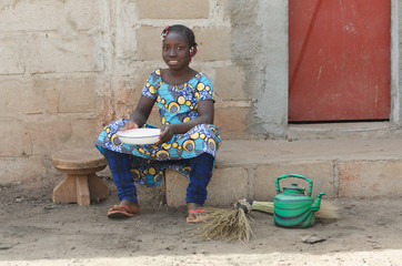 Little African Girl Cooking Rice Outdoors Smiling at Camera
