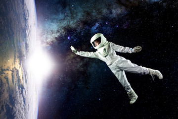 Astronaut in space, in zero gravity near the planet Earth. The concept, find a new earth. Elements of this image furnished by NASA.