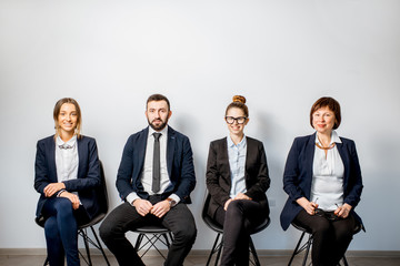 Portrait of a business people sitting in on the chairs in a row on the white wall background