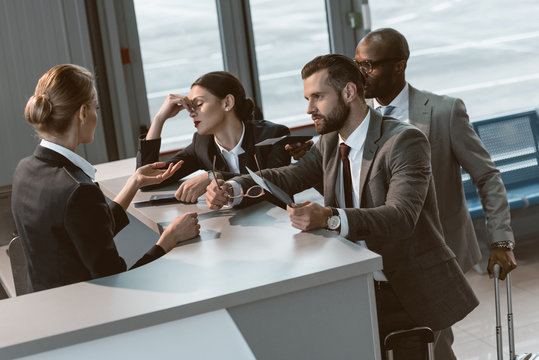 group of angry businesspeople having argument with airport receptionist