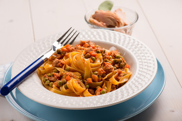 tagliatelle with tuna ragout and green peas, selective focus