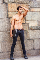 Young East Indian American Man, half naked, showing strong body, wearing black jeans, sneakers, holding laptop computer, standing by rock wall in New York, looking forward..