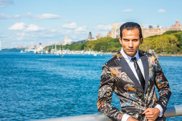 Young East Indian American Man traveling in New York, wearing black fashionable patterned blazer, white shirt, black tie, standing at park by Hudson River. Harbor with boats on background..