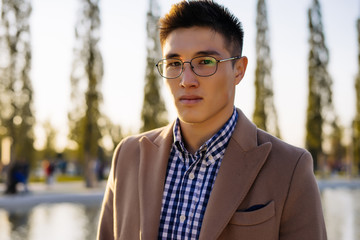 a guy with glasses and a beige coat