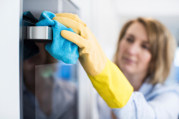 Close Up Of Woman Cleaning Oven In Kitchen