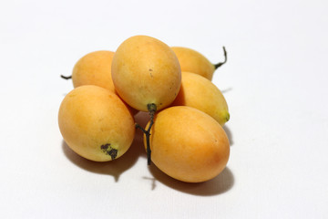 Bouea macrophylla, commonly known as gandaria put stack on white background. The orange color of fruit in tropical zone.