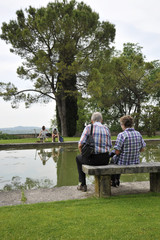 Romantic old couple sitting on park bench by lake. In front of them there is a couple of young lovers who fight.