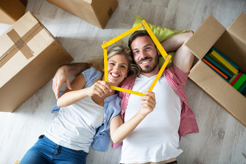Attractive young couple relax between boxes on floor at new apartment